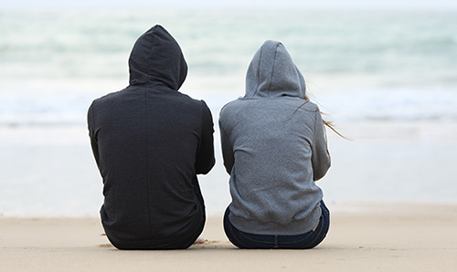 Two young people looking out to sea